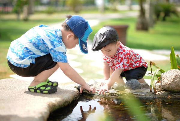 Two children playing near a pond