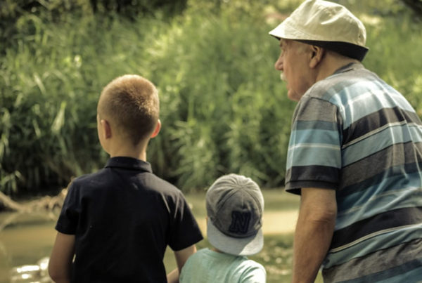 Grandfather with two grandchildren, illustrating the importance of later life planning and drawing upon the wisdom of a financial adviser to help you enjoy retirement